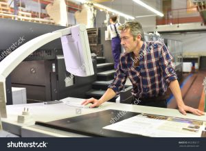 stock-photo-man-working-on-printing-machine-in-print-factory-362290217